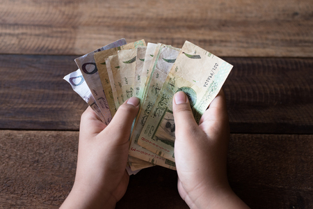 Hand counting Saudi riyal bank notes. Financial and currency concept Stock Photo