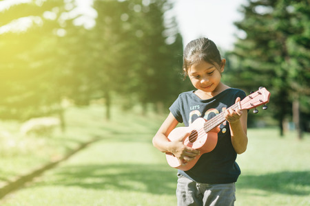 young and happy asian girl playing ukelele guitar in the park at sunny morning. hobbies and tranquility concept Stock Photo