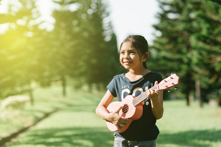 young and happy asian girl playing ukelele guitar in the park at sunny morning while looking to copy space. hobbies and tranquility concept Stock Photo