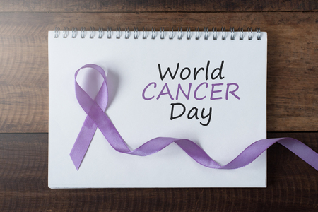 book with WORLD CANCER DAY text and lavender ribbon. symbol of all cancer concept Stock Photo