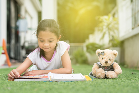 younf asian girl reading a book lying on her house lawn. child education concept