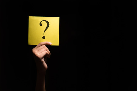 hand holding a yellow paper with question mark in a dark background Foto de archivo
