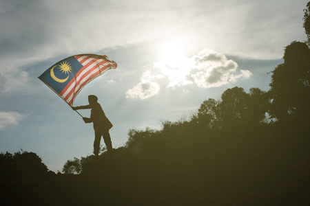 silhouette d & # 39 ; un jeune garçon asiatique tenant le drapeau malaisien célébrer la journée de l & # 39 ; indépendance biélorusse et jour de malaisie Banque d'images