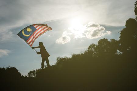 silueta de un niño asiático joven que sostiene la bandera de malasia que sostiene el día de la independencia de malasia y malasia Foto de archivo