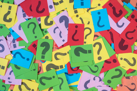 colorful paper with question mark as background. mystery,diversity,questions concept