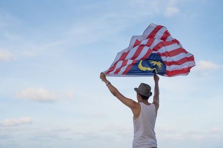 young adult malaysian male waving malaysia flag against blue sky in a windy day