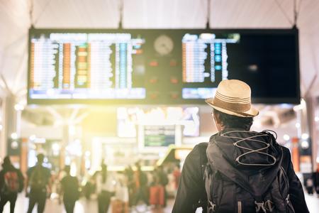 젊은 여행자 또는 관광 비행 일정, 여행, 휴가, 관광 및 휴가 개념에 대한 공항 시간 보드를보고 스톡 콘텐츠