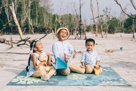 frères et sœurs lisant et riant ensemble à l'extérieur portant des vêtements décontractés. concept de famille, de relation et de style de vie