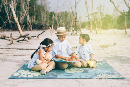 siblings reading and laughing together outdoors wearing casual. family,relationship and lifestyle concept Stock Photo