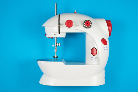 mini sewing machine isolated on blue background. fashion and tailor concept