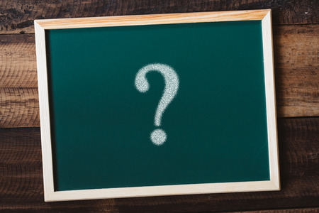 chalkboard written QUESTION MARK on wooden table. learning,study,school,FAQ,asking and question concept
