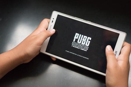 petaling jaya, selangor, malezja – 31 lipca 2018 r.: chłopiec trzymający cyfrowy tablet grający w mobilną grę online o nazwie PUBG, słynną strzelankę online dla dzieci i nastolatków. Publikacyjne