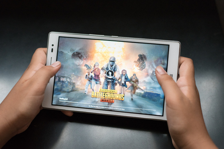 petaling jaya, selangor, malaysia - 31 July 2018 : a boy holding a digital tablet playing online mobile game called PUBG, a famous online shooting games between kids and teenagers. Stock Photo - 116661266