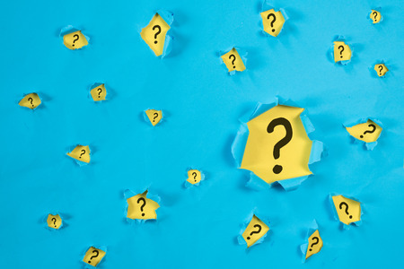 Torn blue paper revealing QUESTION MARK on yellow paper. concept of questions, faq, q&a, problem, riddle and quiz background