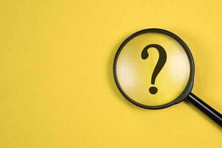 노란색 배경에 초점을 맞춘 QUESTION MARK가 있는 돋보기. 검색 및 연구의 개념입니다.