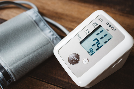 Petaling Jaya, Selangor, Malaysia - 14 March 2019 : Sphygmomanometer or electronic blood pressure from brand OMRON on a wooden desk. Omron is a well known company in manufacturing medical instrument Редакционное