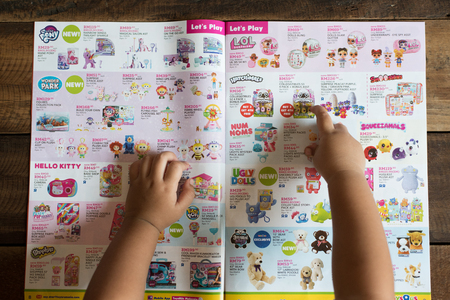 Petaling Jaya, Selangor, Malaysia - 16 March 2019 : Child hand pointing at her dream toy on a TOYS RUS brochure, asking for a birthday gift. toys r us is a famous company selling toys.