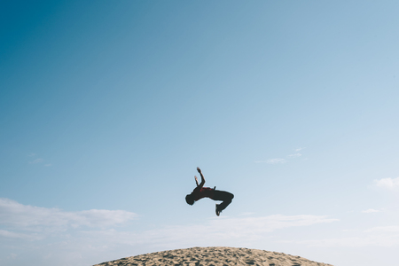 young men doing a acrobatic backflip move look like he is floating mid air on a sand dune. concept of freedom, happiness, health and tranquility