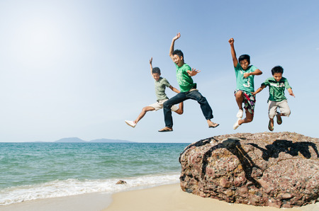 four asian male teenager jumping and having fun at the beach. concept of togetherness and friendship Фото со стока