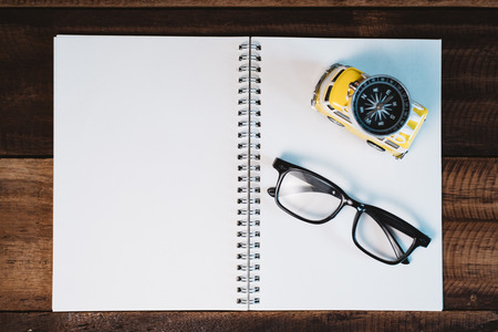Eyeglasses, compass, book and toy miniature minivan on a wooden table. Concept of travel, holiday, wanderlast and vacation planning Фото со стока