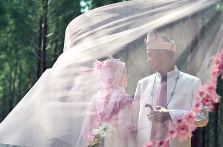 creative photoshoot of a malay loving couple bride and groom on their wedding wearing a traditional malay dress Stock Photo