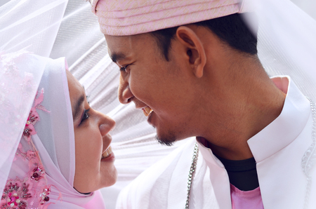 close up portrait of a malay bride and groom under veil with lovely emotion. Concept of malay wedding and marriage 版權商用圖片