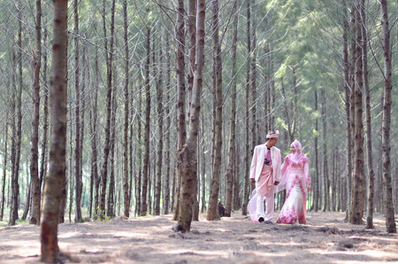 creative outdoor photoshoot of a malay loving couple bride and groom on their wedding wearing a traditional malay dress