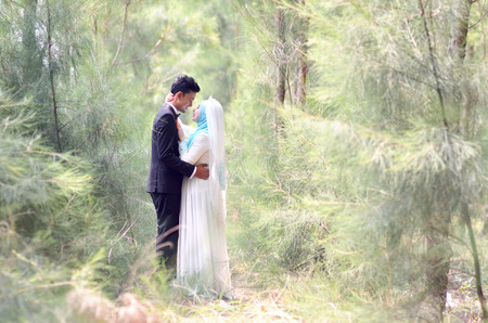 Outdoor portrait of a beatiful malay bride and groom couple in a garden. Concept of wedding and relationship
