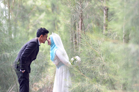 Outdoor portrait of a lovely malay wedding couple in a beautiful park. concept of love, relationship and wedding