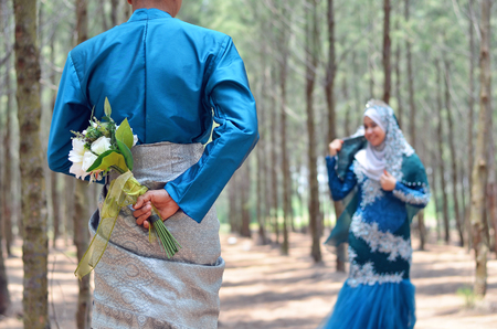 close up of a groom holding a wedding flower bouquet looking at her bride. concept of malay wedding and relationship