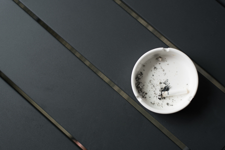 Close-up of a burning cigarette in a ashtray. Concept of health and lifestyle Фото со стока