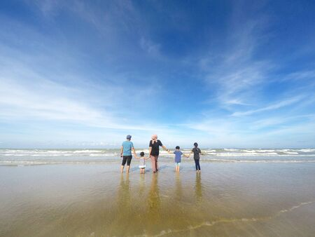 rear view of family with three children standing over beautiful blue sky. Concept of family, happiness, parenting and relationship