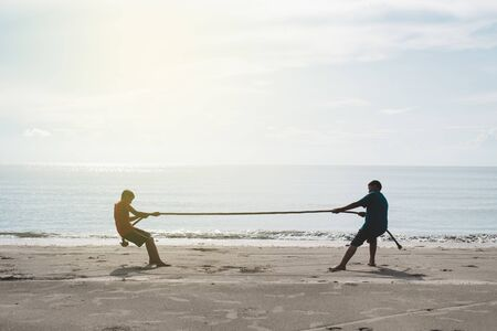 two asian kids pulling a rope at the beach. concept of friendship and competition