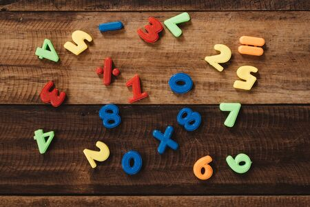 group of colorful numbers and mathematical notation on wooden table. concept of math learning and education Фото со стока