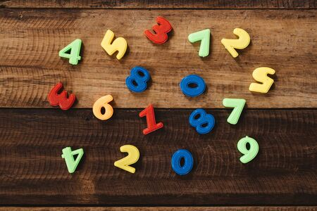 multi colored toy numbers on a wooden table. Concept of mathematics, education and child learning