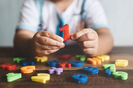Child holding plastic toy number one, she is learning to count. Concept of child education and child growth
