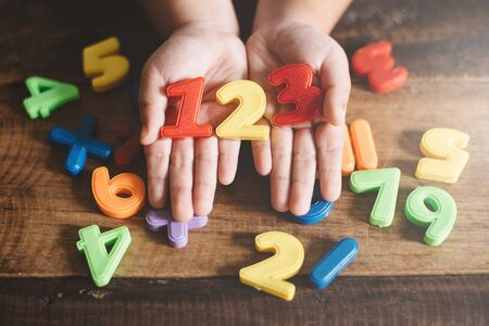 child hands showing a colorful 123 numbers agains wooden table. Concept of Child education, learning mathematics and counting Фото со стока