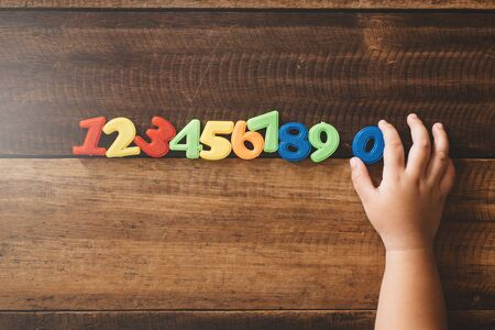 Child hand holding number zero with sets of other colorful numbers plastic toy on a wooden table. Concept of child learning numbers and child education Фото со стока