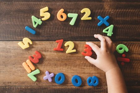 child hand holding a colorful plastic toy numbers on a wooden table. children learning counting numbers 123. concept of early education
