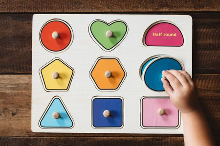 Child matching a toy shape puzzle on wooden table. Concept of early education and child development