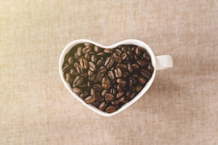directly above view a heart shape mug of a raw roasted coffee beans. Concept of Favorite drink and coffee addiction