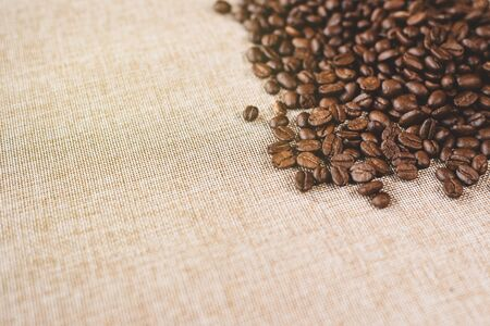 high angle view of a heap of a fresh rosted coffee beans on a burlap sack. concept of favorite drink Фото со стока