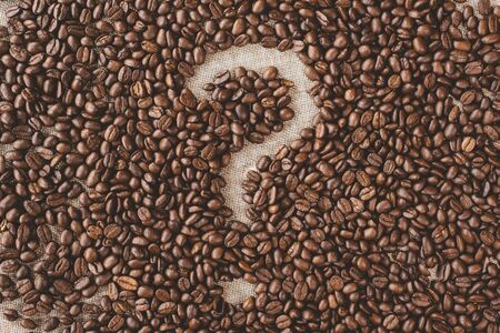 Question mark symbol made from a coffee beans on a burlap sack. concept of which type of coffee and questions Фото со стока