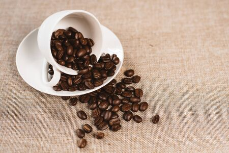 coffee beans overflow on a white cup over a burlap sack. concept of favorite drink and agriculture