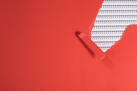 red paper teared revealing question mark on white paper. concept of FAQ, Q&A, search, riddle and information