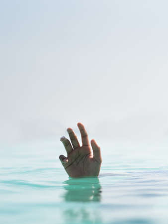 rotated image of a hand sinking in a water. concept of helpless, drown, loneliness 免版税图像