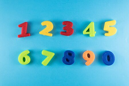 group of numbers from plastic toy against blue background. concept of learning to count for children and mathematical numerals