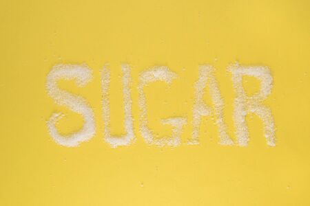 sugar written on yellow background. concept of diabetes, unhealthy eating and health care Foto de archivo - 130026154