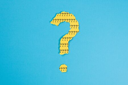 question mark symbol from a teared yellow paper on a blue background. Concept of FAQ, Q and A, Questions and riddle Foto de archivo - 130026155