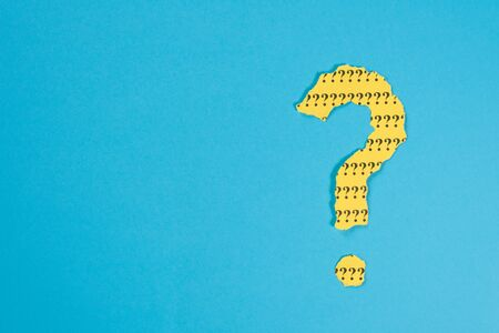 question mark symbol from a teared yellow paper on a blue background with copy space. Concept of FAQ, Q and A, Questions and riddle Foto de archivo - 130026160